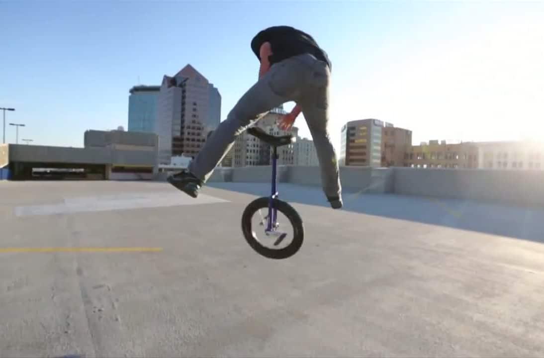 Cette image montre un homme sautant avec un monocycle